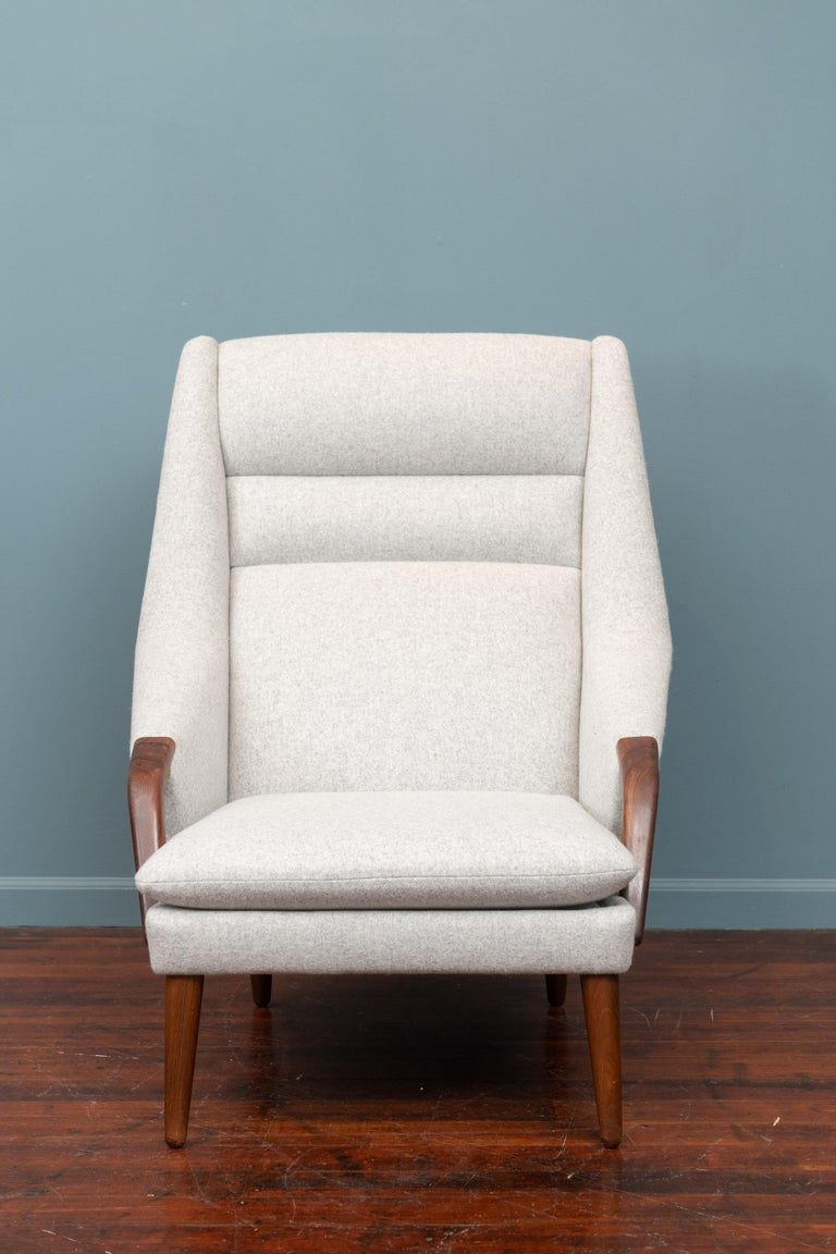 Scandinavian Modern high back lounge chair with highly grained rosewood arm pads and newly upholstered in light grey felt.