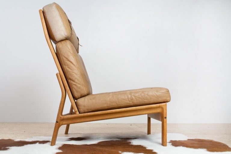 Comfortable lounge chair from Scandinavian origin in manner of Hans Wegner, yet is was made by Komfort, a Danish manufacturer. This piece of Danish design is made of solid oakwood in a very warm color. The upholstery is original and made of high