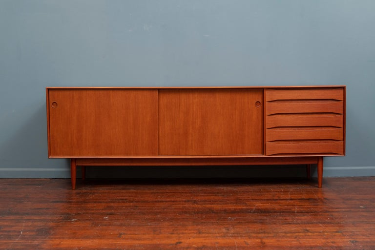 Scandinavian modern large solid teak credenza. High quality cabinetry details in the dovetail construction, made from solid teak boards, five sculpted drawer fronts and a finished back.