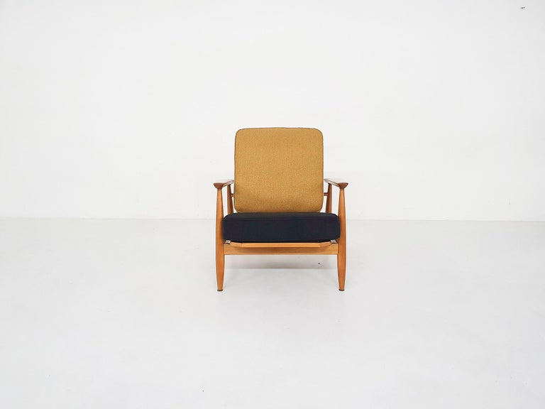 Scandinavian Modern spindle back lounge chair with arm rests from the 1960s.  The designer is yet unknown, but the design remind us of the Domus 1 lounge chair by Alf Svensson for DUX. We re-upholstered the cushions in black and ochre. The frame