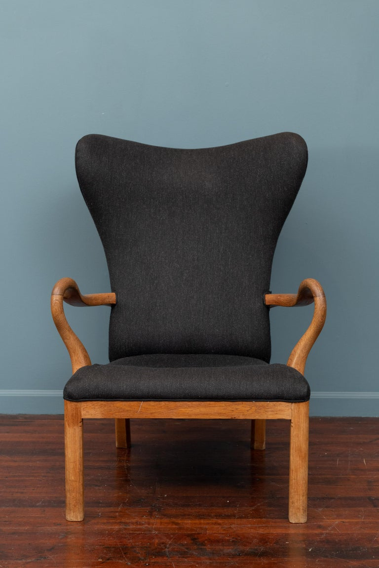 Scandinavian Modern lounge chair made in a solid oak frame. Unusual design by a talented unknown maker with newer upholstery, super comfortable.