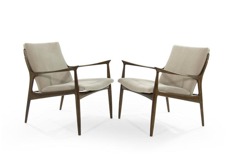 Pair of sculptural Danish modern lounge chairs designed by Ib Kofod-Larsen. Sculptural frames fully restored. Seat and backrest newly upholstered in natural mohair.
