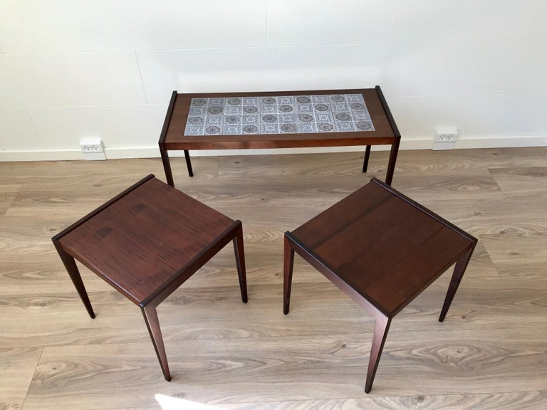 A nest of tables fashioned from teak and dark oak. The rectangular main table has inlaid tiles from Royal Copenhagen. Very practical if used as a coffee table group since the tiles allows wet and hot drinks etc. being served without any protection.