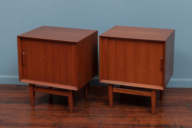 Pair of Scandinavian Modern teak nightstands with tabor doors and contrasting blonde interiors. High quality design and construction newly refinished and ready to install.