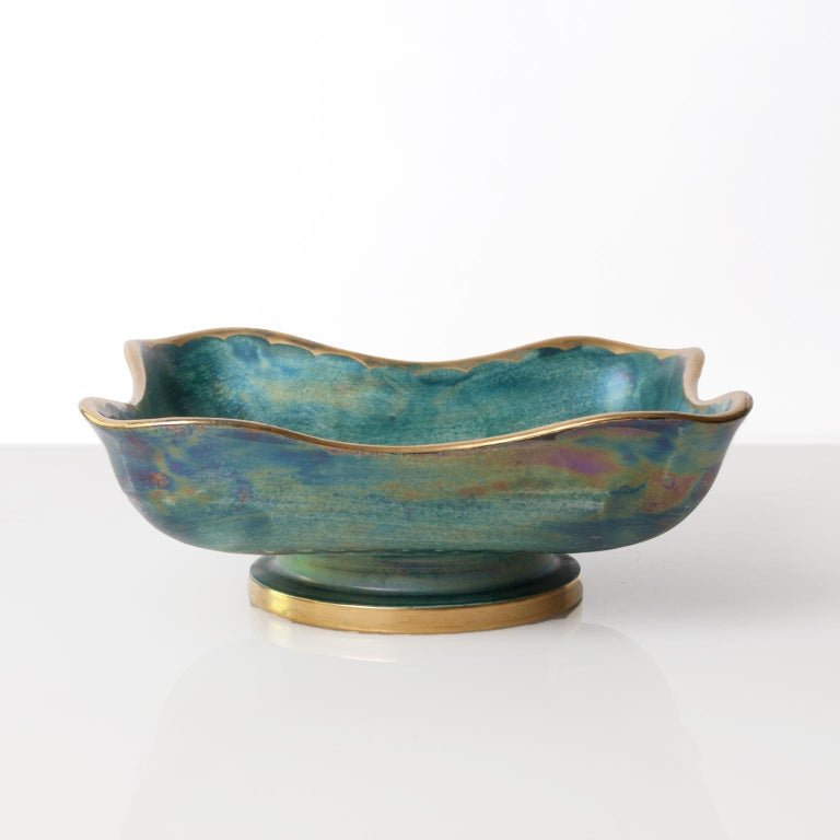 Scandinavian Modern ceramic bowl with a soft organic form with a luster glaze in blue and green and a hand-painted floral design and trim in gold. Designed by Josef Ekberg for Gustavsberg, Sweden, signed and dated 1936.   Measures: Height 3.25