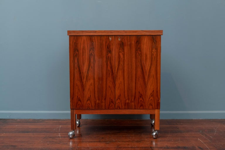 Scandinavian Modern rosewood bar cabinet or cart designed by Torbjorn Afdal for Bruskbo, Norway. Flip top for double the serving area with racks for glasses and bottles etc. In very good original condition with matching key.