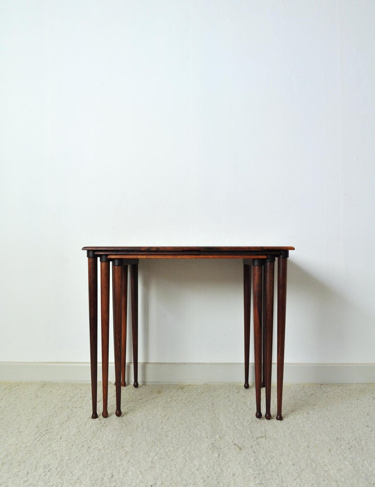 Scandinavian Modern nesting tables with drumstick legs in rosewood by Danish BC Møbler. Labeled by maker and Danish Furniture makers control. Fine vintage condition with small signs of wear. Dimensions: H 49.5 cm x W 60 cm x D 38 cm H 48 cm x W