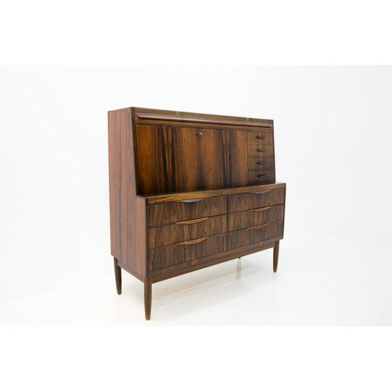 Scandinavian modern, secretary cabinet by Ib Kofod-Larsen features a rare, exotically grained rosewood finish with beautifully sculpted drawer handles and tapered legs. The top front opens into a desk space revealing a variety of drawers, shelves