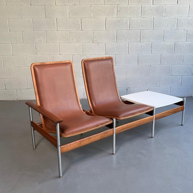 Scandinavian Modern, two-seat with side table ensemble designed in 1959 by Sven Ivar Dysthe for Fjord Fiesta, Norway features a tubular steel and walnut frame with vinyl upholstery and white formica tabletop. Table is 14 inches height.