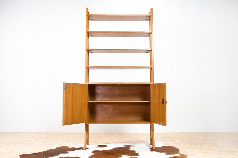 Typically Scandinavian Modern design: a robust yet spacious and well constructed wall unit in natural brown oak with solid wooden uprights. The unit is modular and you can vary the position of the cabinet and shelves. All in very good condition,