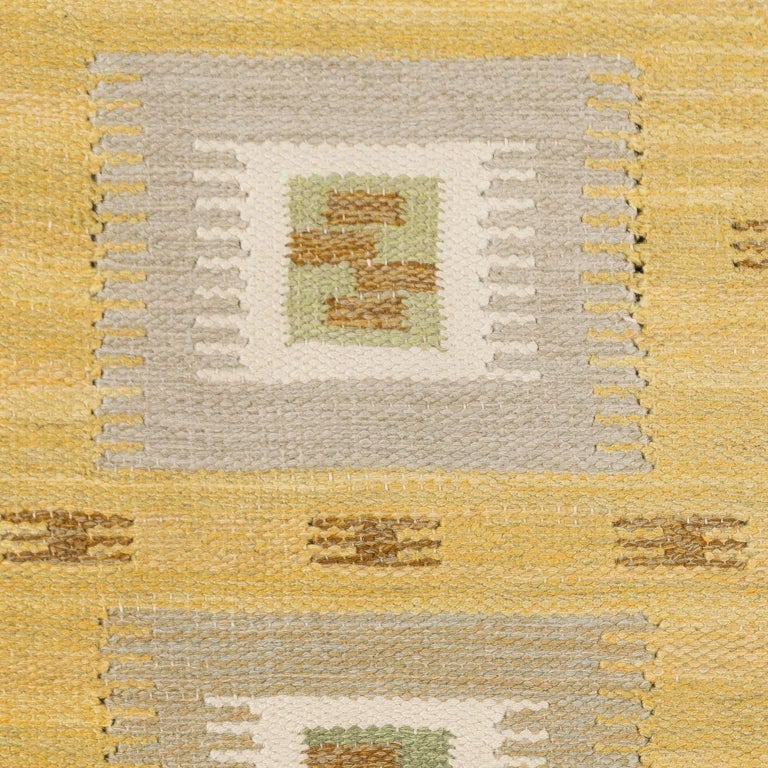 Beautiful geometric decor in Yellow, grey, green and brown tones. This rug is from Nk-textilkammare (NK-textile chamber) flat-woven Swedish rug, executed in a single interlocking tapestry technique. Signed NKT (Nk textile chamber). The department
