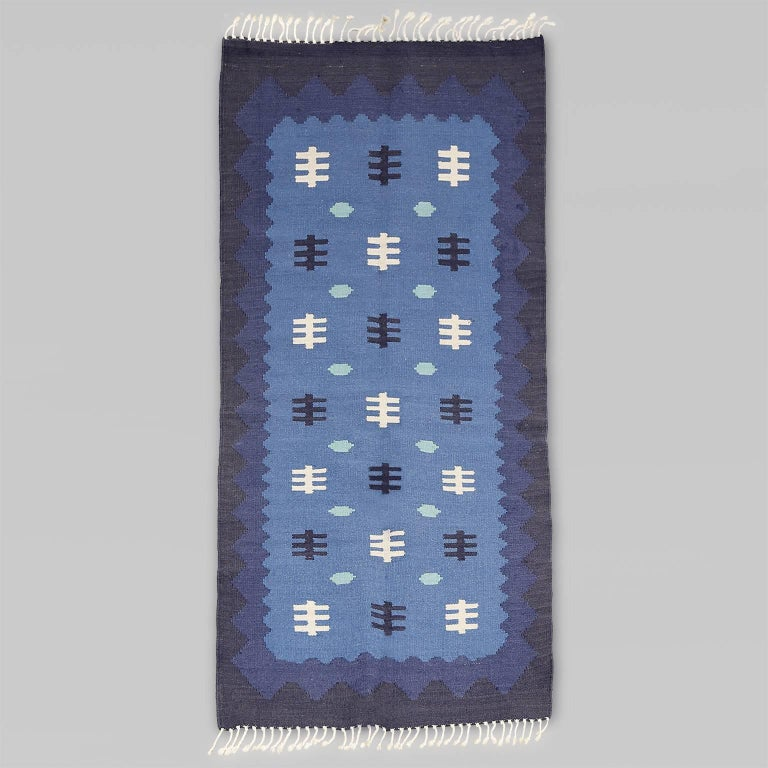 """Scandinavian Modern, Swedish Mid-Century Modern wool flat-weave rug with a graphic design in light, medium and dark blue, finished with white fringe. Professional cleaned.   Measures: Measures: Length 71"""", width 35""""."""