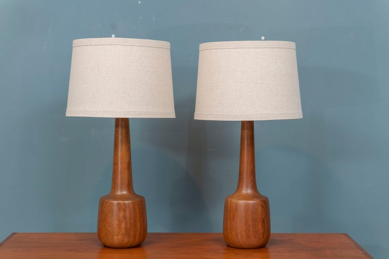 Scandinavian Modern turned teak table lamps with new wiring and shades, ready to enjoy.