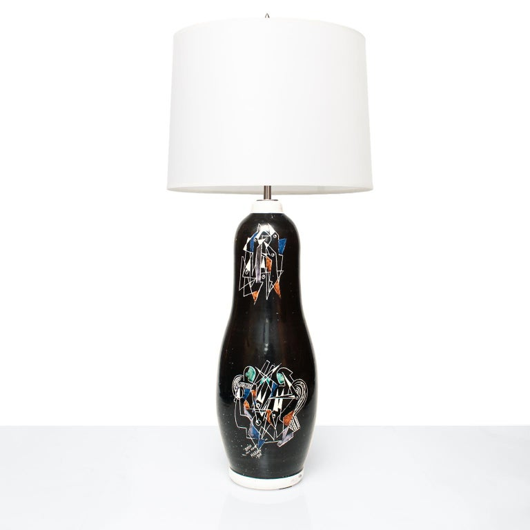 A Scandinavian Modern tall ceramic lamp by Marian Zawadzki for Tilgmans Keramik. The lamp's body is a black glaze which is hand decorated with 2 scenes depicting birds feeding their young in a nest. Signed