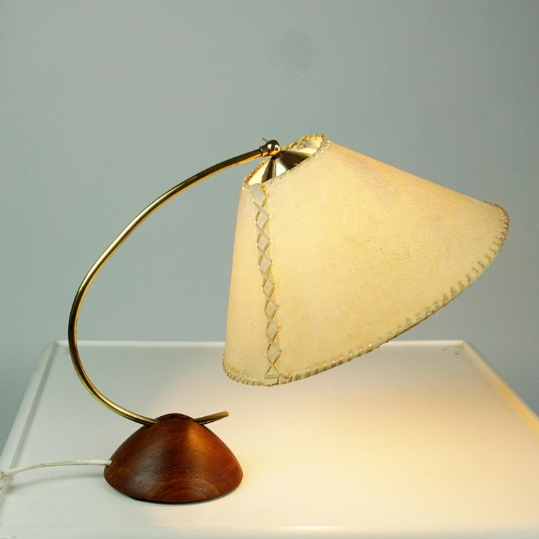 A charming small Scandinavian Modern brass table or desk lamp in a sculptural shape. it´s base is hand-turned from a single teak block of richly grained and warmly toned texture and its stem and fittings are made of brass. It still has its original