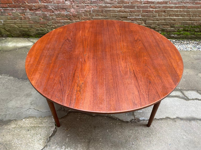 Scandinavian design teak and oak dining table with one large leaf, circa 1960-1965. Teak round top with tapered solid oak legs. Freshly oiled. Good condition overall with the runners sliding easily, some minor light scratches and some bruising on