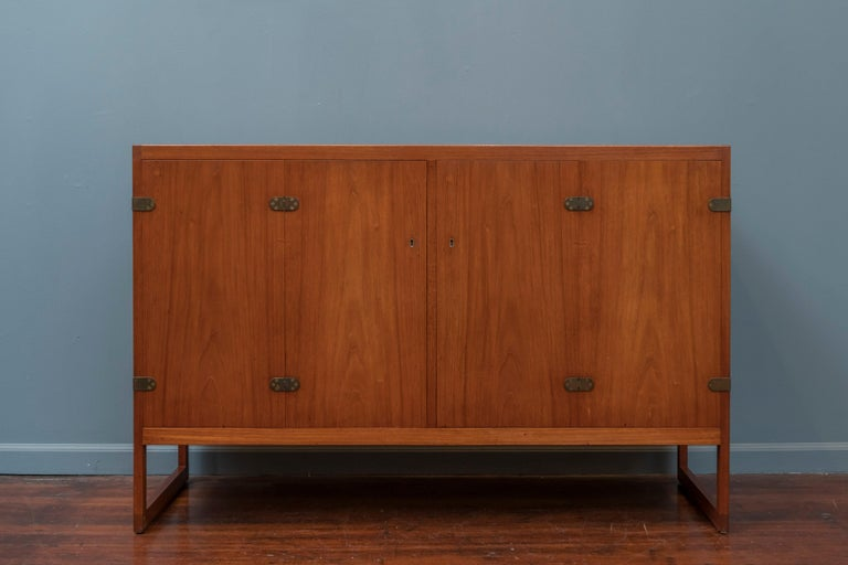 Scandinavian Modern teak cabinet, elegantly understated and designed by Borge Mogensen for P. Lauritsen and Son. Two bi-fold doors open to reveal four oak finger-jointed drawers and two shelves. The exposed brass hinges on this piece add just the