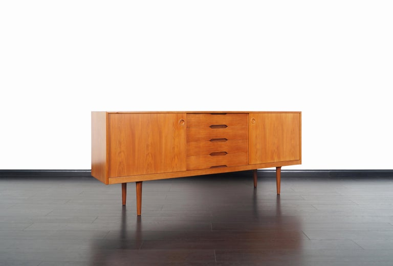 Norwegian modern teak credenza designed by Alf Aarseth for Gustav Bahus, Norway, circa 1960s. This skillfully crafted credenza is comprised of two sliding doors with adjustable shelves and four dovetailed drawers in the center, all integrated with