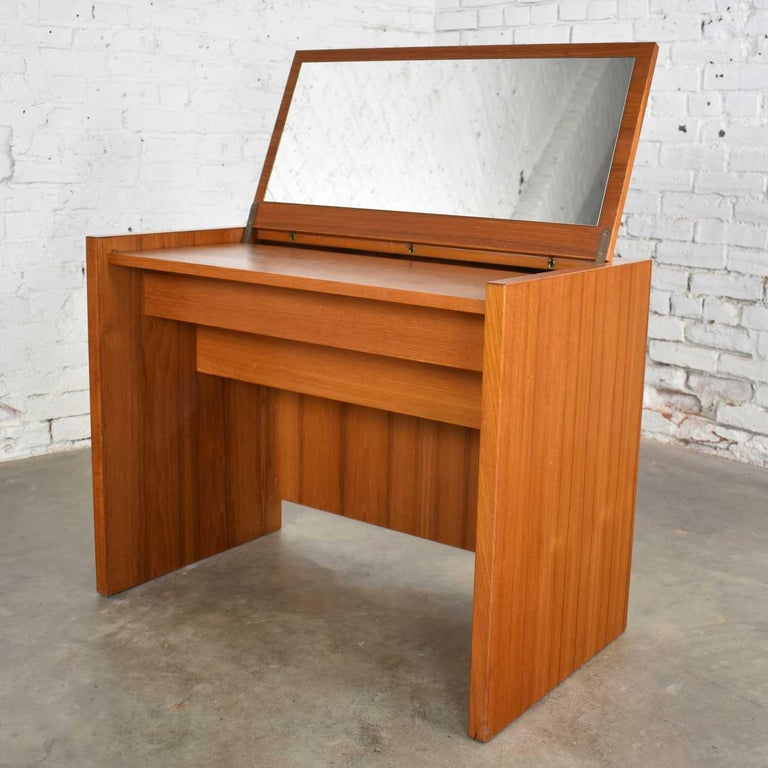 Wonderful Scandinavian Modern teak flip open top vanity with mirror by Jesper International of Denmark. It is in beautiful vintage condition with one small mark on the left top edge, possibly a burn from a curling iron. The finish has been restored