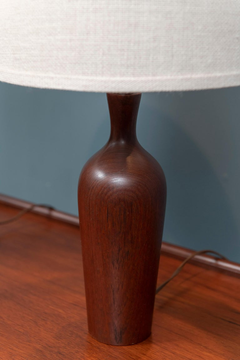 Scandinavian modern teak table lamps, sculpted solid teak bodies with nude grass cloth shades.