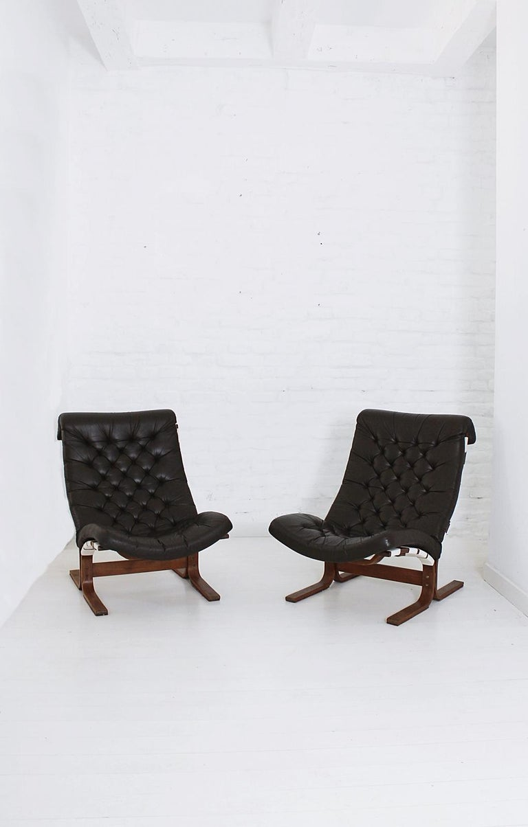 Stylish comfortable Scandinavian Modern high back lounge chairs with stained bentwood frames and tufted dark brown leather upholstery. Sold separately.