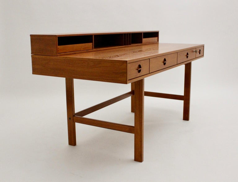 This presented Scandinavian modern vintage teak writing table or desk was designed by Jens Quistgaard, circa 1969 and executed by Lovig Dansk. This vintage teak flop top partner desk is very functional. You are able to fold it at one side for using