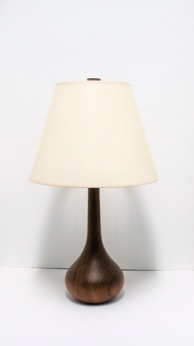 A beautiful Scandinavian or Danish modern organic shaped teak wood lamp with original wood finial, circa mid-20th century Denmark or Scandinavia. Off-white vintage shade included.   Lamp measurements:  8