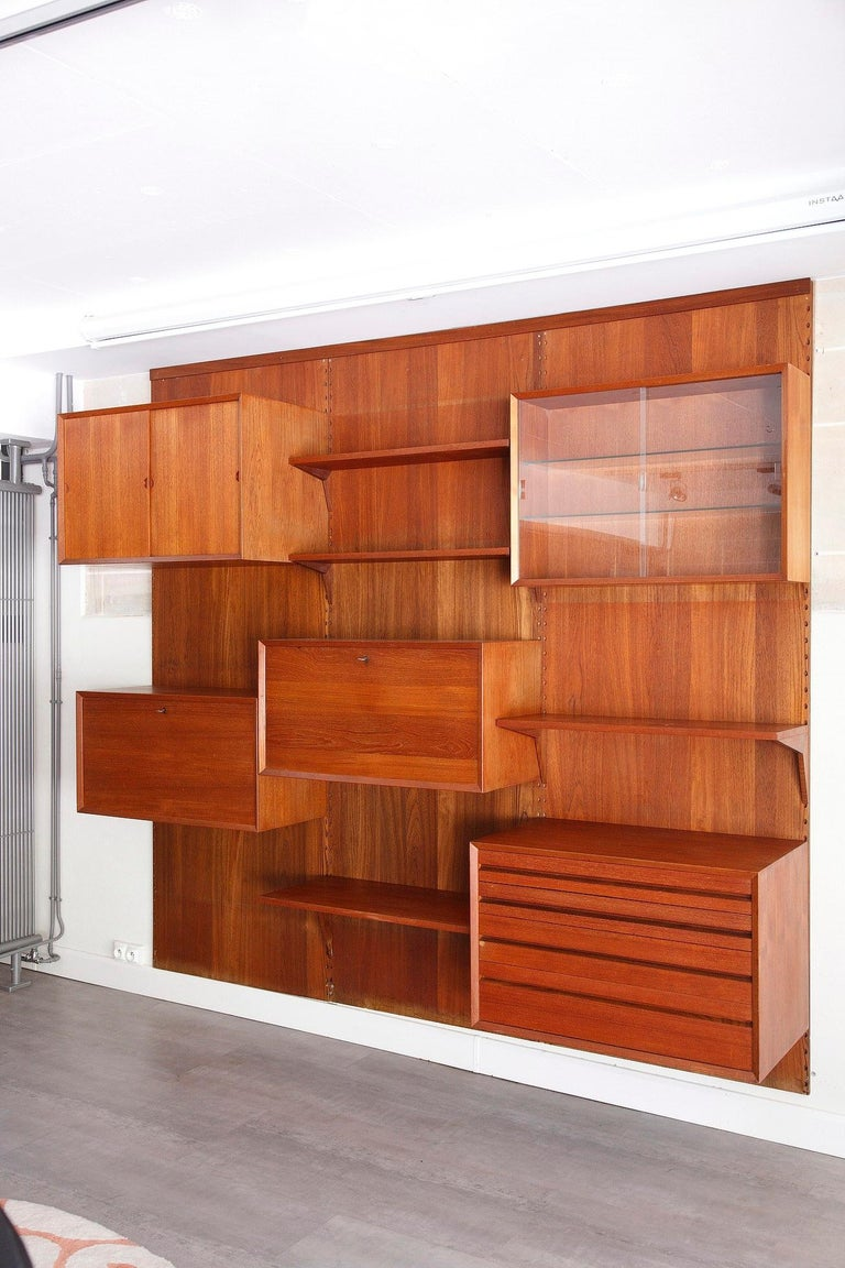Scandinavian wall unit designed by Poul Cadovius in the 1960s, crafted of teak, provided with wooden fixations. It is composed of three vertical ladders with 4 shelves and 5 containers as follow:  - 2 shelves (P 22cm, L 80cm) - 1 shelve (P 38cm,