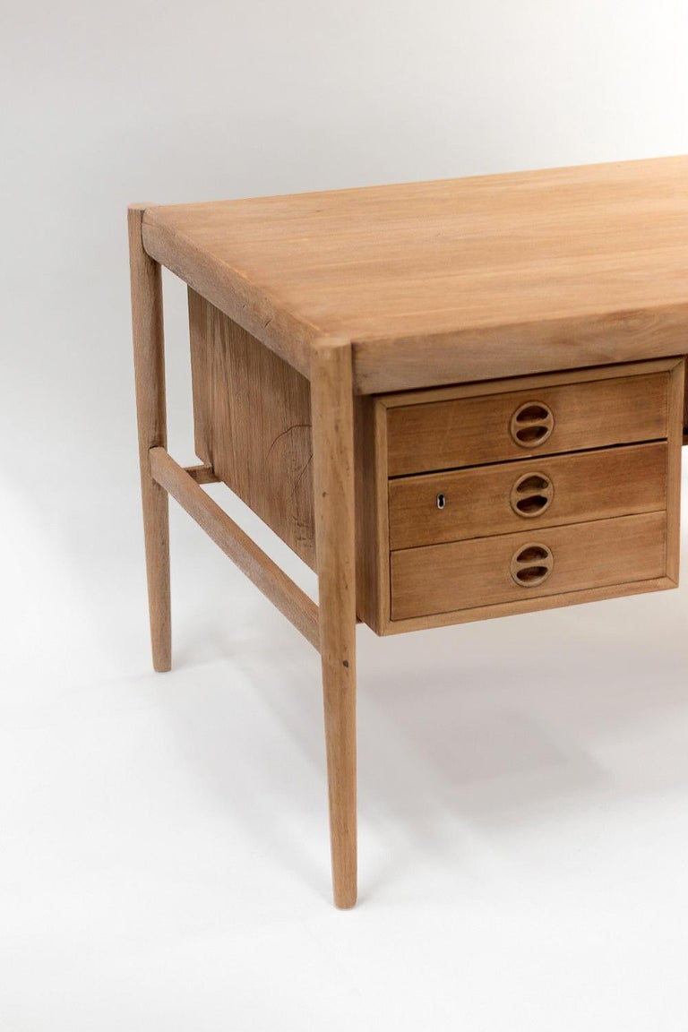 Scandinavian natural teak desk made of two boxes with three drawers each. Rectangular top standing on four cylindrical legs: uprights detached from the boxes under the tray. Circular handles inside drawer's facade.  Scandinavian work realized