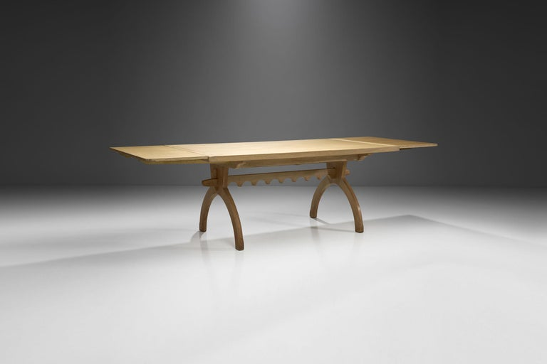 This impressive Scandinavian table is defined by its natural material, seamless joinery and distinctive, but soft ornamentation on the bottom.   Albeit the table is made of solid wood, the oak's light color and the slender lines create an airy