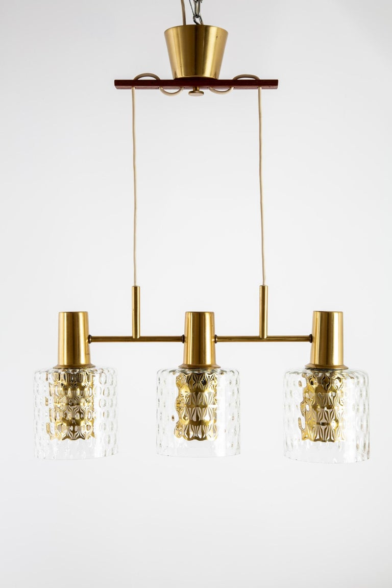A Scandinavian Modern pendant lamp. The frame system is of brass. The shades are of bubbled glass. Total width is 52 cm and height is 23 cm. Inclusive a brass ceiling piece.