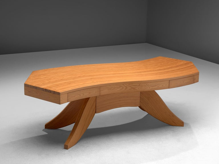Writing table, pine, Scandinavia, 1960s.  Stunning biomorphic table with a waved tabletop. This writing table features a waved wooden top, made out of tangentially-sawn pine slats. Two drawers are included in the tabletop. The centered leg extends