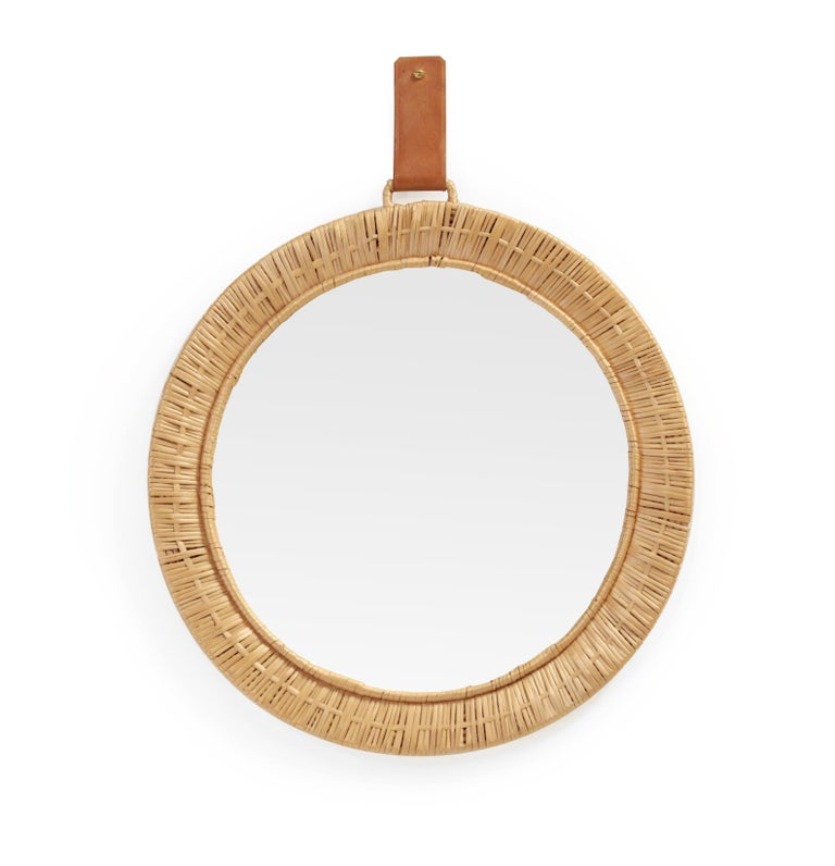 Decorative and organic mirror in rattan with leather wall hanger. Most likely design and made in Finland from circa 1950s first half. The mirror is in in very good vintage condition.