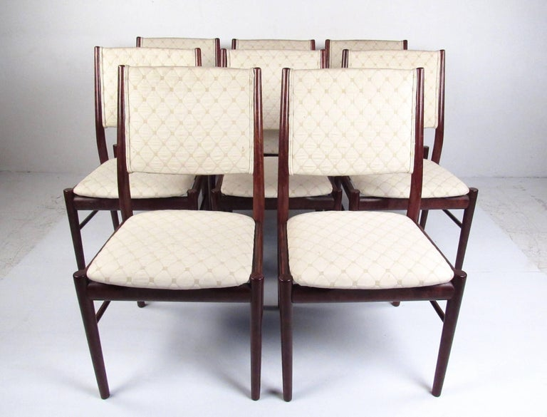 Matching set of eight vintage modern dining chairs and expandable rosewood dining table make an elegant statement in any dining room space. This impressive Scandinavian construction by Skovby includes sturdy high back chairs with feature comfortably