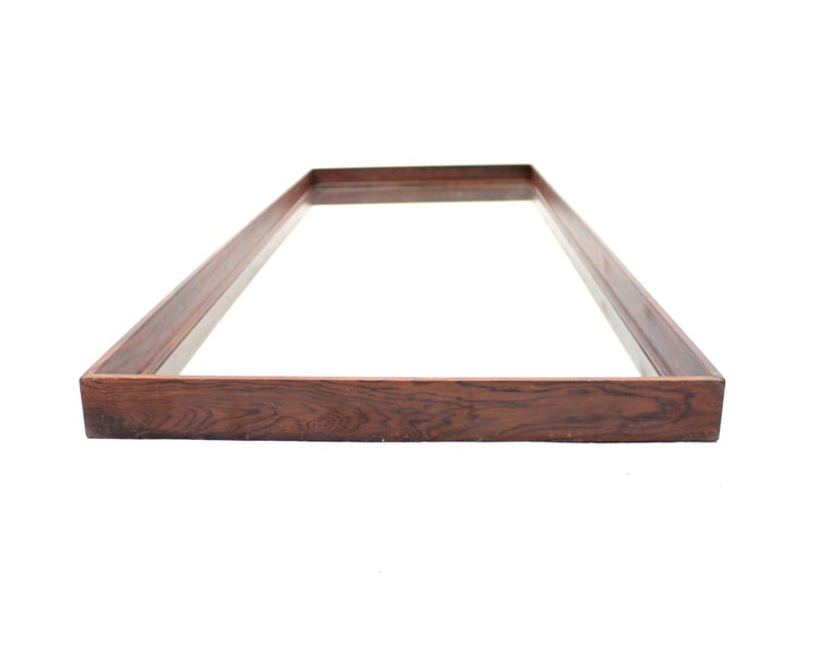 Swedish box shaped rosewood mirror made in the 1960s. The frame is only 1 cm thick but measures 5 cm in depth with the mirror on the bottom witch makes it very light in appearance. Good vintage condition with light ware.