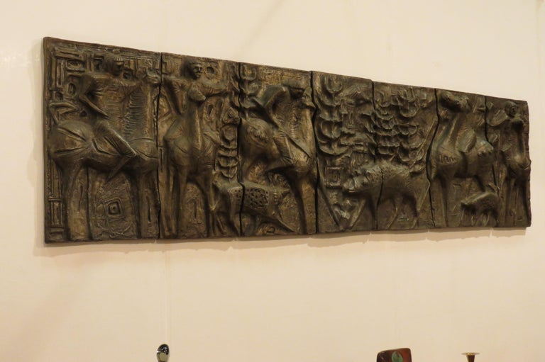 A unique wall hanging of a boar hunting scene dating from the 1960s.   The scene consists of seven individual panels that sit alongside each other to form an impressive, sculptural piece of wall art.  Made from cast resin allowing it to be hung