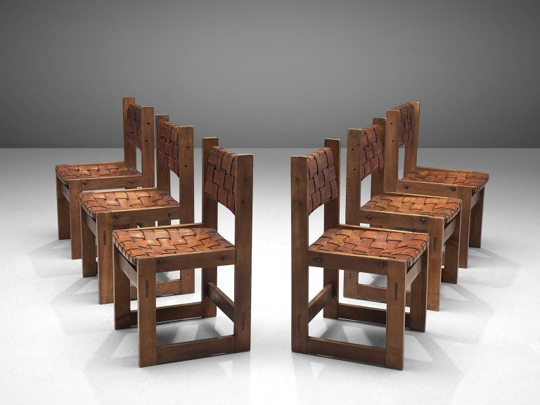 Set of 6 dining chairs, elmwood and patinated leather, Scandinavia, 1922.  A set of midcentury dining chairs in thick saddle leather. The woven seats and backrests consist of cognac leather straps that aged beautifully, resulting in an admirable