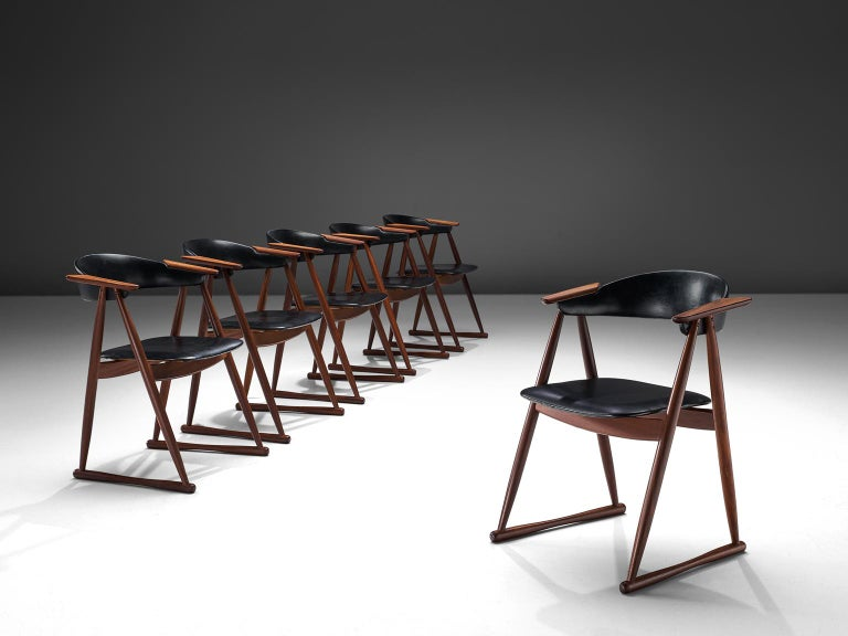 Set of six dining chairs, black faux leather and teak, Denmark, 1960s.  This set of dining chairs are made by cabinet maker Randers Møbelværk in the 1960s. The playful design features protruded armrests that lean on triangular shaped frame. At the