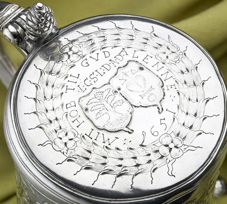 A Scandinavian silver tankard, Norwegian or Danish, maker's mark only I intersecting S, perhaps Johan Schluter of Bergen, circa 1650 on three pomegranate feet, chased with scroll foliage on a matted ground, the lid with contemporary accolle arms,