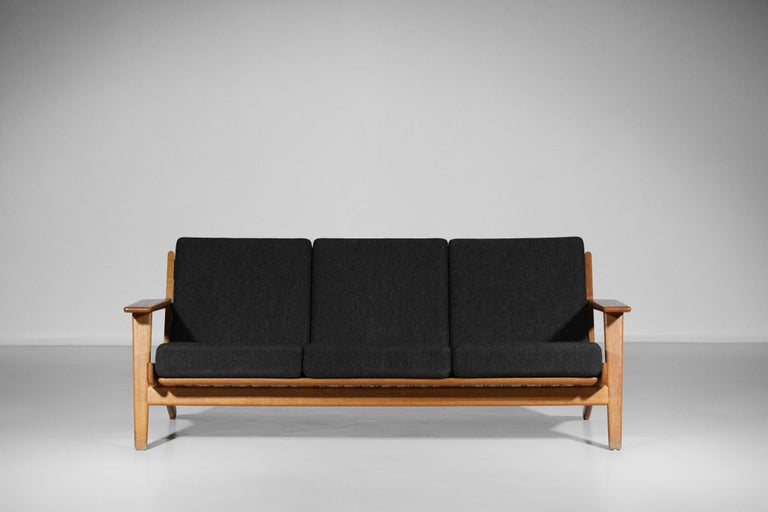 Scandinavian sofa GE 290 by the famous Danish designer Hans Wegner, published by GETAMA in 1955. Solid oak frame, sloping legs and slightly sloping backrest optimize the seating comfort typical of this 3-seater model. Original cushions