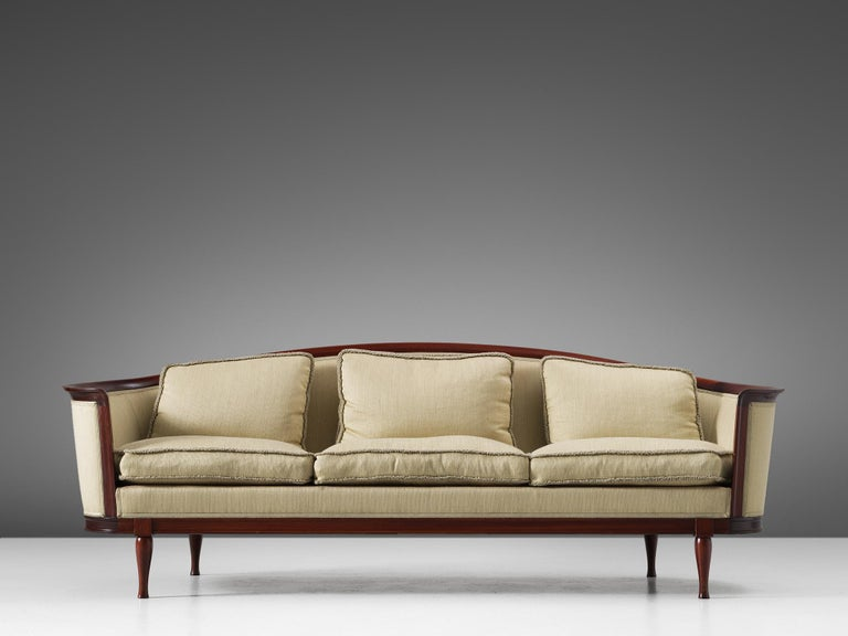 Sofa, in mahogany and fabric, Scandinavia, 1930s.  Luxurious Scandinavian sofa, with a variety of well designed lines and stunning details. Note the elegant curves that gives this sofa its characteristic look. Emphasized by the mahogany wooden frame