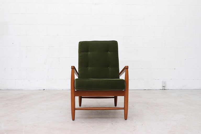Modernist stick back lounge chair with olive velvet cushions and new seating straps on teak frame. Good original condition with wear consistent with age and use.