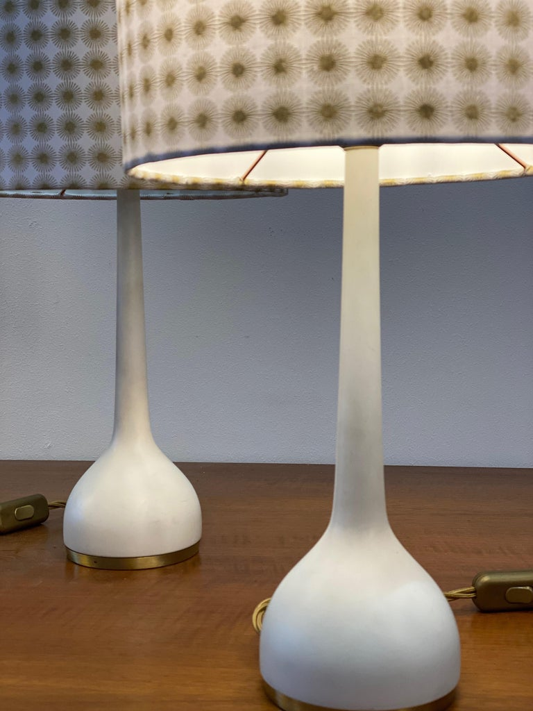 These table lamps were designed by Hans-Agne Jakobsson in the 1960s and manufactured by Hans Agne Jakobsson AB in Markaryd, Sweden. It comprises a white lacquered base with original fabric shades. The bas as well as the shades are marked with the
