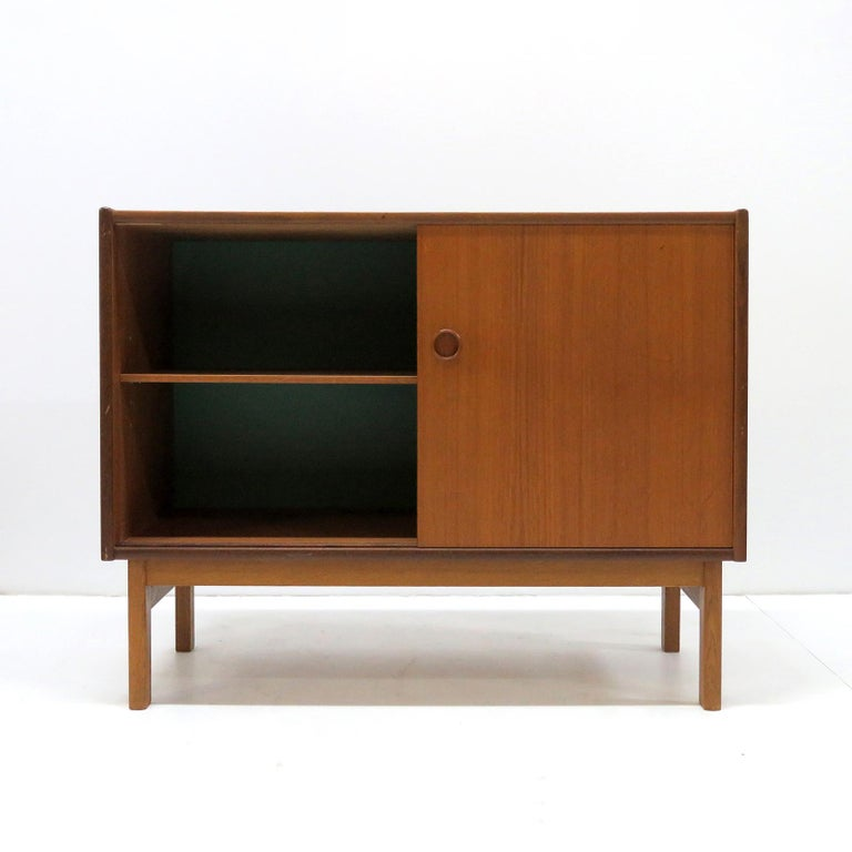 wonderful small-scale 1960s Danish sideboards/dressers in teak on an oak frame, with one adjustable shelf behind two sliding doors, the inside of the back wall is teal colored. Priced individually.