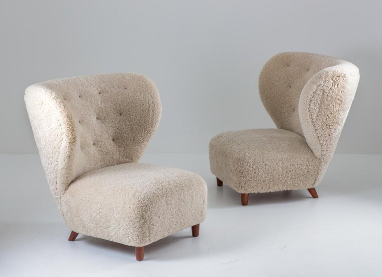 Pair of oversized sheepskin chairs by Danish cabinet maker, circa 1930. These amazing chairs looks beautiful from any angle. They have been upholstered in off-white sheepskin with cognac leather buttons.  Condition: Excellent, fully restored and
