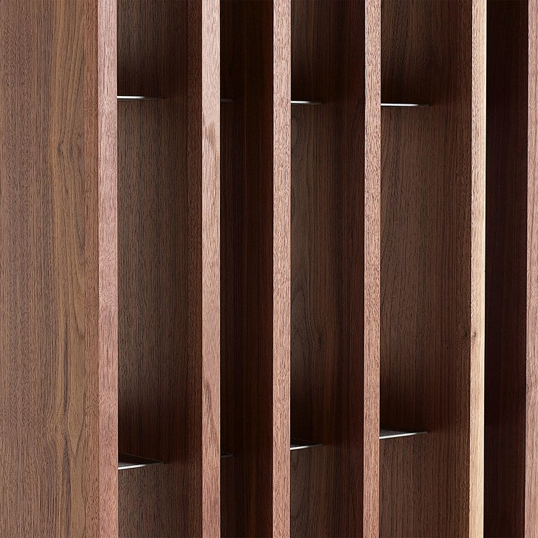 Minimalist and sophisticated, this bookcase by Studiomartino5 is a testament to contemporary, skillful craftsmanship. Its slender and geometric silhouette is composed of six vertical panels made of Canaletto walnut-veneered plywood crossing six
