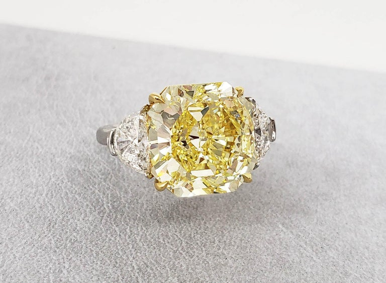From SCARSELLI, this spectacular 10.05 carat Fancy Intense Yellow Radiant Cut Diamond is GIA graded Internally Flawless and classically set with a matched pair of white half moon diamonds F-G color and VS+ clarity.  This ring may be sized or