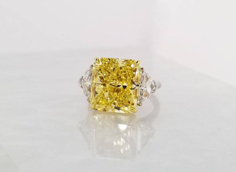 This Beautiful Classic Ring From Scarselli features a 10 carat Fancy Vivid Yellow Radiant Cut Diamond with GIA certificate 2165563315 (See certificate picture for detailed stone information). The center diamond is guarded by 2 half-moon white