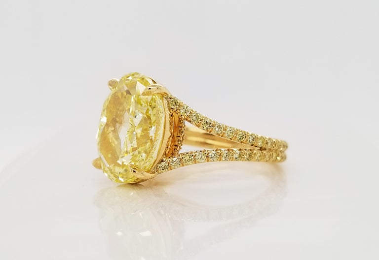 From SCARSELLI, a simply important ring featuring a 6.00 carats Fancy Intense Yellow Oval cut diamond (GIA VS2 Clarity Certificate 5202490787) surrounded by 0.48 carats of Fancy Intense Yellow Round brilliant diamonds in a coordinating handmade
