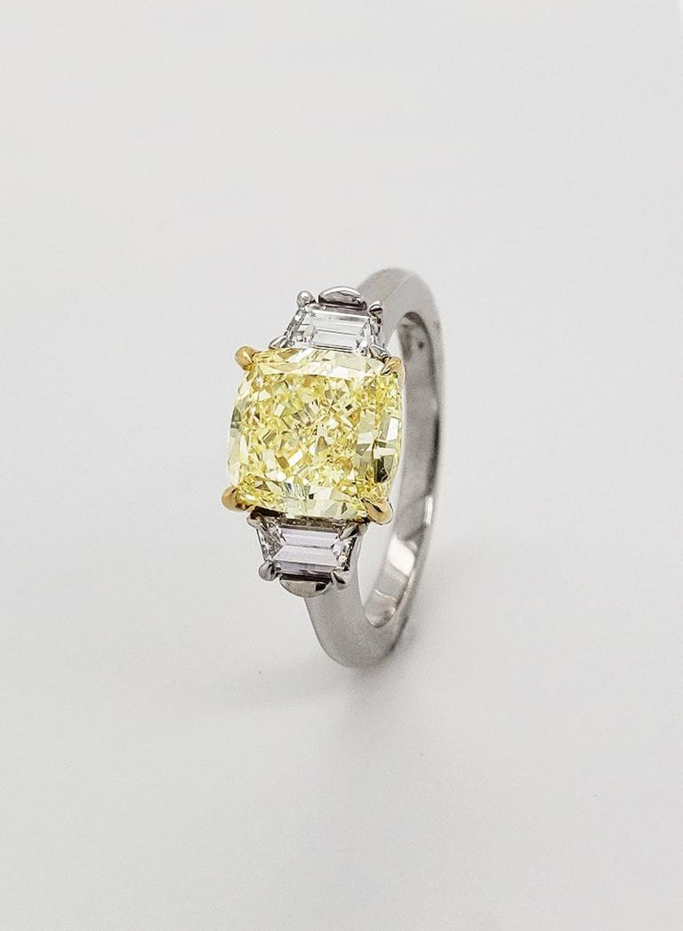 From SCARSELLI, this delightful and versatile Fancy Light Yellow Cushion cut diamond of VVS2 clarity is flanked by .43 carats in white trapezoid diamonds.  A classic and upscale look that never goes out of style and transitions from day to evening